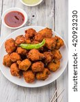 Small photo of Delicious Tasty and Yummy Indian Moong Dal vada or moong dal pakoda or moong vade or Pakora (Fritter) with fried green chilli, red and green hot sauce.
