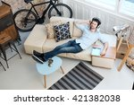 young man lying on sofa at home ... | Shutterstock . vector #421382038