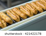 Small photo of Yellow eclair shells. Narrow conveyor line with eclairs. Quality over quantity. Product that sells well.