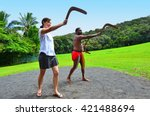 Small photo of Yirrganydji Aboriginal warrior teaches a young woman how to throw a boomerang during cultural show in Queensland, Australia.
