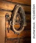 Small photo of Antiquity equine Tack: strap, burden, halter, rein, braided bit, harness, martingale, drawgear, bell hang on rusty nails in dark wooden blockhouse. View closeup with space for text on brown backdrop