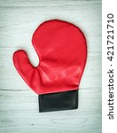 Small photo of Red boxing glove on the wooden background. Leisure activity. Aggressive sport.