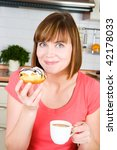 young woman enjoying a cup of coffee and doughnut - stock photo