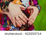 parents hands on the belly of...   Shutterstock . vector #422053714