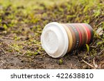 Small photo of POZNAN, POLAND - MARCH 23, 2016: Paper cup with coffee lying on green grass affecting the environment