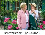 Small photo of Three Quarter Length Portrait of Two Smiling Senior Women Talking Together in Garden with Bright Pink Flowers