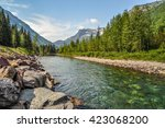 A river runs down from the mountains that guard a valley in Glacier National Park, Montana.