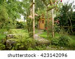 Stock photo garden idyll with a garden shed and rose arch with blooming red roses 423142096