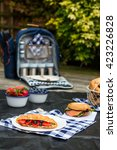 Small photo of Picnic setting with freshly baked croissant with berries, fresh strawberries and blueberries, sandwiches and bagel laid out on a dark blue checked cloth and hamper backpack
