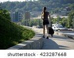 Stock photo woman walking dog 423287668