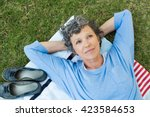 pensive senior woman lying on... | Shutterstock . vector #423584653