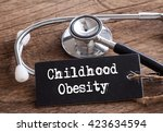 Small photo of Stethoscope on wood with Childhood Obesity word as medical concept