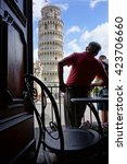 Small photo of A man admiring the Leaning Tower of Pisa, viewed from a cafe, Tuscany, Italy