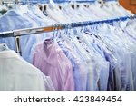 weighs clean clothes on hangers ... | Shutterstock . vector #423849454
