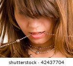 beauty girl face close up, bite chain - stock photo