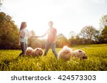 young couple with the dogs in... | Shutterstock . vector #424573303