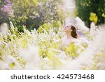beautiful girl in a big spirea... | Shutterstock . vector #424573468