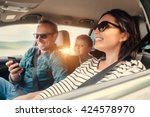Small photo of Happy family riding in a car