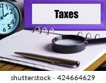 Taxes - Purple Office Folder on Background of Working Table with Magnifying glass,  a pen and clock -business and finance concept