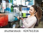 Stock photo happy brunette girl choosing domestic aquarium in pet shop 424761316