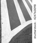 Small photo of Black asphalt pavement painted with white stripes