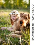Small photo of Girl teenager with flower headband sitting and relaxing with her dog airedale terrier at field in sunset light