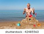 Elderly Man Is Building A Sand...