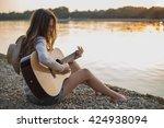 Girl Playing Guitar While...