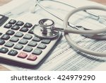 Small photo of Vintage color of Health care costs. Stethoscope and calculator symbol for health care costs or medical insurance