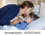 mother giving good night kiss... | Shutterstock . vector #425022403