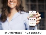 smiling woman showing a mobile... | Shutterstock . vector #425105650