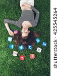 Small photo of NOVI SAD, SERBIA- MAY 17, 2016: Young woman lying on the grass with Facebook, gmail, Instagram, Wikipedia, YouTube and other application icons. Editorial Use Only