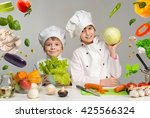 two smiling children cooks by...