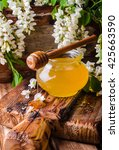 Small photo of Acacia honey in gar on wooden background. Spring mood. Selective focus. Toned image