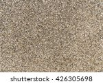 Small photo of Exposed aggregate concrete in closeup made of small pebbles in different brown and gray color shades