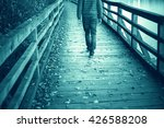 Small photo of A man walking alone on aged wooden bridge floor with leaves on the ground. Man walking alone across the wooden aged bridge. Cyan blue color effect used. Selective focus used.