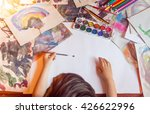 Small photo of A boy is painting with left hand. Colorful paintings on the desk.