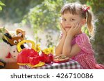 Stock photo pretty little girl drinks tea with her toy friend in garden 426710086