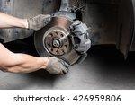 Car mechanic hands replace brakes in garage. Mechanic technician worker installing car wheel at maintenance.  Worker changing brake disc. Brake disc installation concept. - stock photo