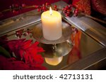 candle burning in moody Balinese interior setting - stock photo
