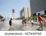 Small photo of Seoul, South Korea - May 27, 2016: Admiral Yi Sun Shin statue at Gwanghwamun square and kids playing with water.