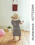 Small photo of Baby girl with stripey dress and straw hat, vintage filter