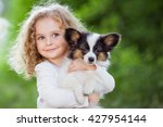 Stock photo little curly girl with a papillon puppy outdoor summer 427954144