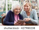 Small photo of Female Neighbor Showing Senior Woman How To Use Digital Tablet