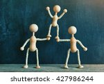 Small photo of Two wooden little men supporting the third. Concept of teamwork, friendship, support or family
