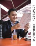 Small photo of Chinese business man reading a newspaper and drinking a cup of coffee while sitting with his phone in an Asian food court or Hawker centre cafe.