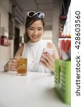 Small photo of Chinese woman drinking an ice lemon tea, while sitting with her phone in an Asian food court or Hawker centre cafe.