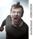 Small photo of Single man in a brown shirt looking angry screaming with tor hair and jumpy