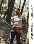 Small photo of portrait of aggressive muscular male lumberjack, woodworker with chainsaw in hand, posing