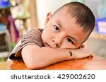 Small photo of Child making a sad face.Boy has a black birthmark on the arm In Sad mood. Mercury Float with emotion